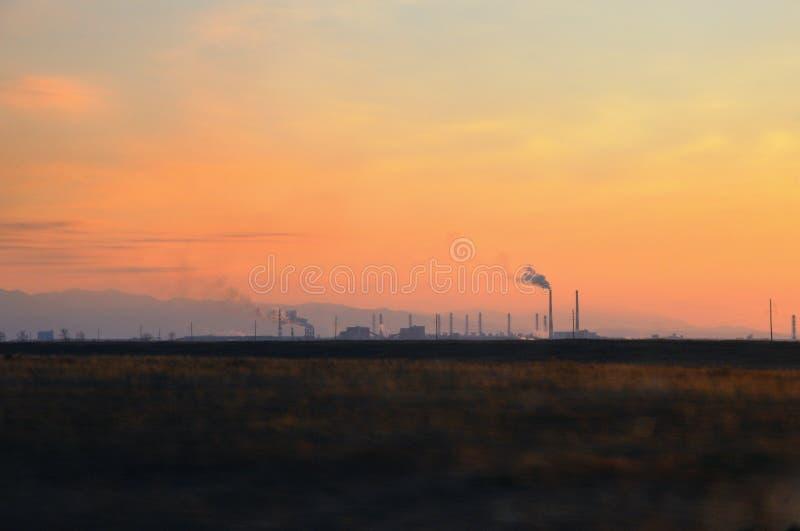 Höstlandskap med den metallurgical växten med tung rök från rör bak ett fält under spektakulär färgrik solnedgång royaltyfria foton