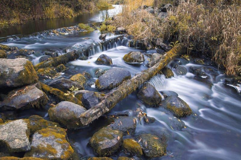 Höstlandskap med floden som flödar slätt mellan mossiga stenblock royaltyfri fotografi