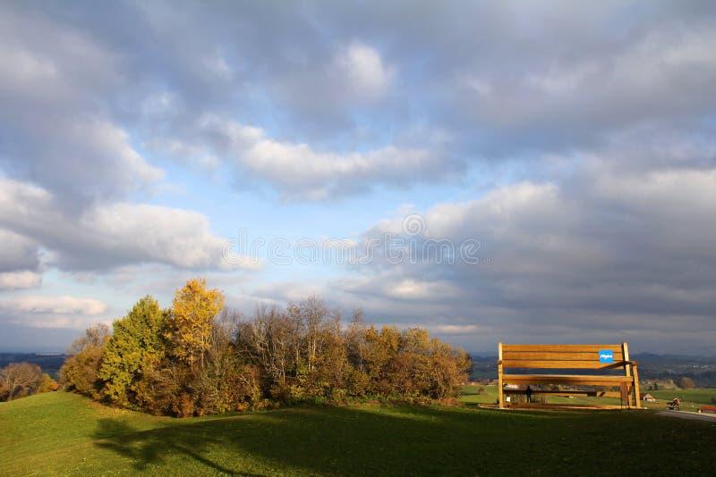 Höstlig panorama med en stor träbänk royaltyfri fotografi