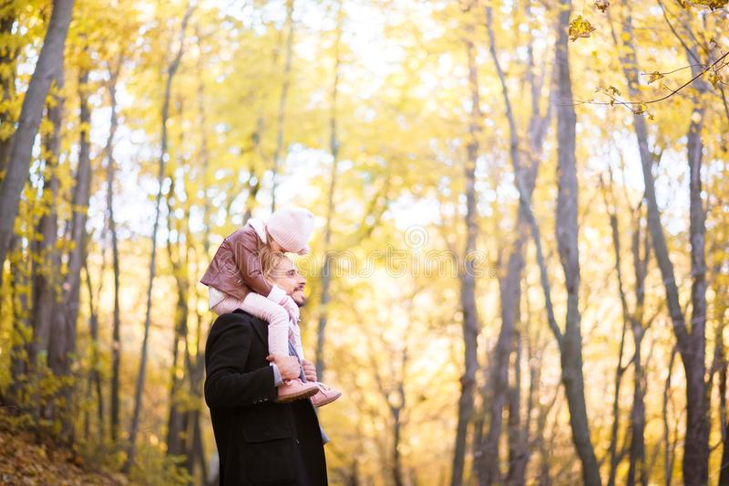 Höstmode för barn och den hela familjen En liten dotter sitter på skuldrorna av fadern i halsen mot bacen royaltyfria foton