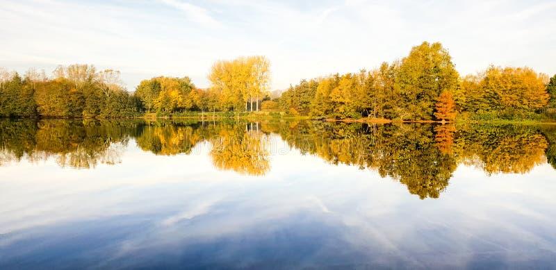 Höstplats på en sjö med reflexioner av träd i vattnet royaltyfri foto