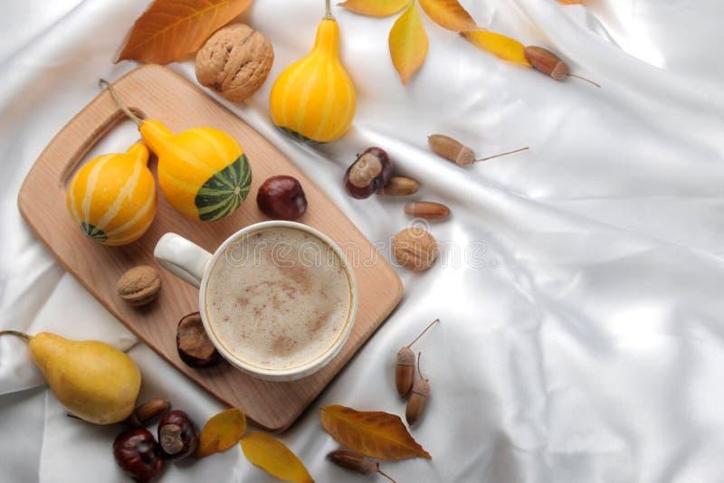 Höstsammansättning med varma kaffe- och gulingsidor och dekorativa pumpor på ett magasin, på en säng ovanför sikt royaltyfria bilder