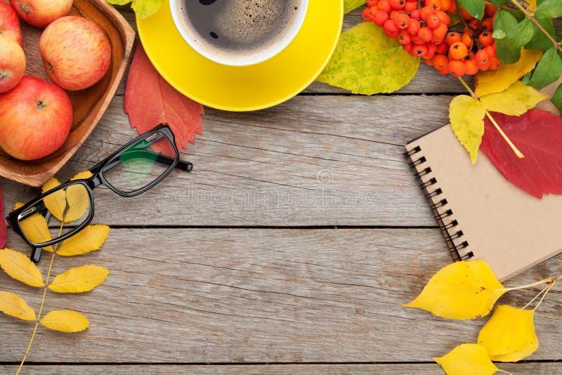 Höstsidor, äpplefrukter, kaffekopp och notepad royaltyfri bild