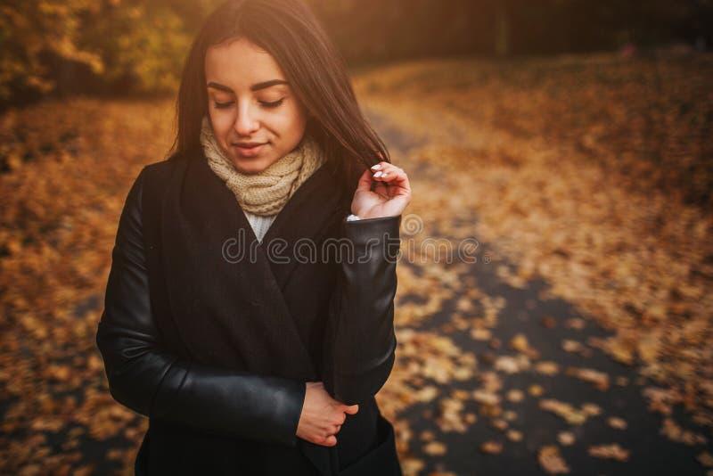 Höstsidor som faller på lycklig ung kvinna i skogstående av den mycket härliga flickan i nedgång, parkerar royaltyfri fotografi