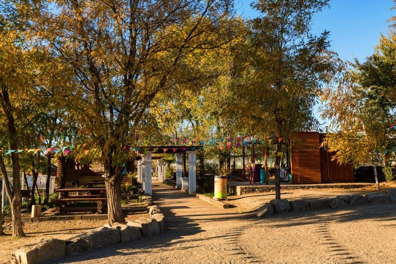 Höstsikten av flodstranden parkerar med trähus och bänkar arkivbild