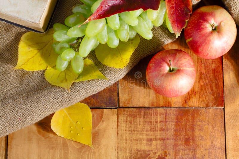Höstskördäpple, druvor och gulingsidor på trätabellen arkivfoto