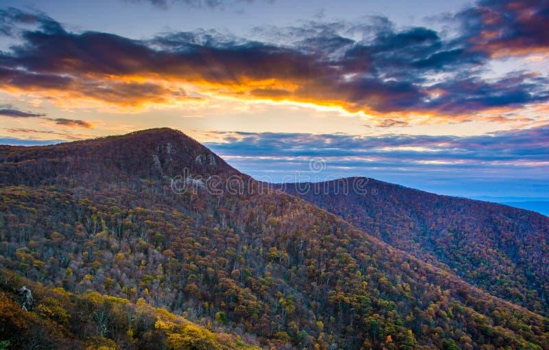 Höstsolnedgång över det Hawksbill berget som ses från horisontdrev I arkivbilder