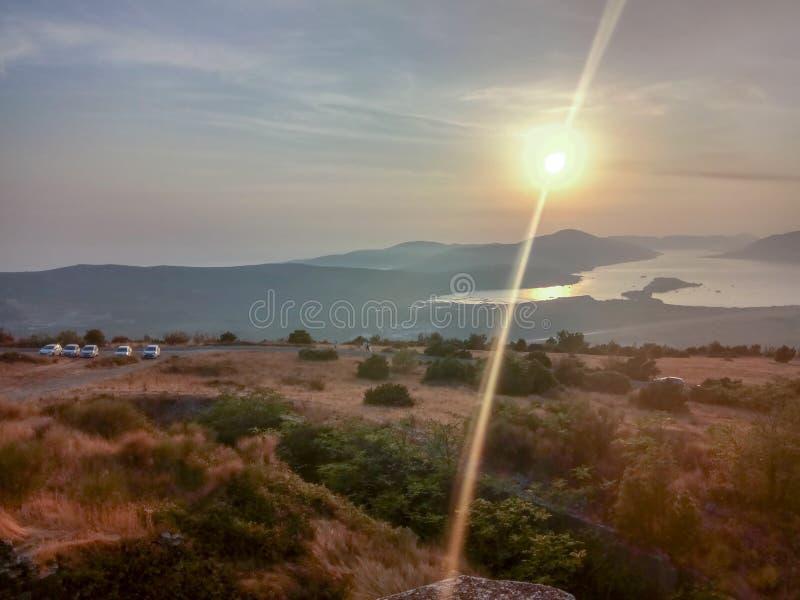 Höstsolnedgångplats av ett berg och ett hav Montenegro arkivfoton