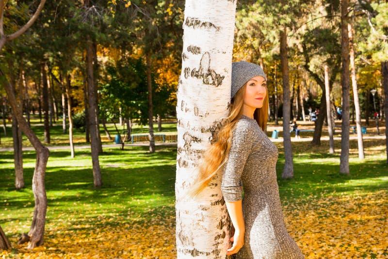 Höststående av den härliga kvinnan över gulingsidor, medan gå i parkera i nedgång Positivt sinnesrörelser och lyckabegrepp arkivbilder