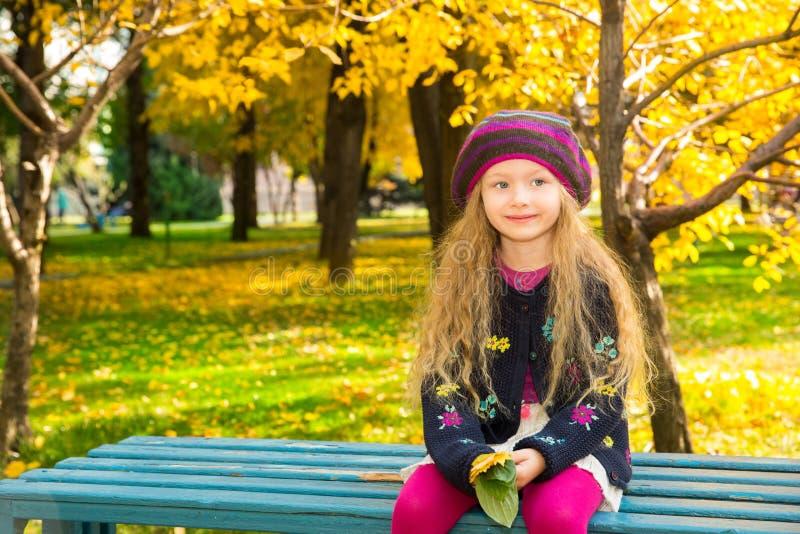 Höststående av det härliga barnet Lycklig liten flicka med sidor i parkera i nedgång royaltyfria foton