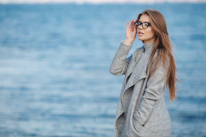 Höststående av en härlig kvinna på havskusten arkivfoto