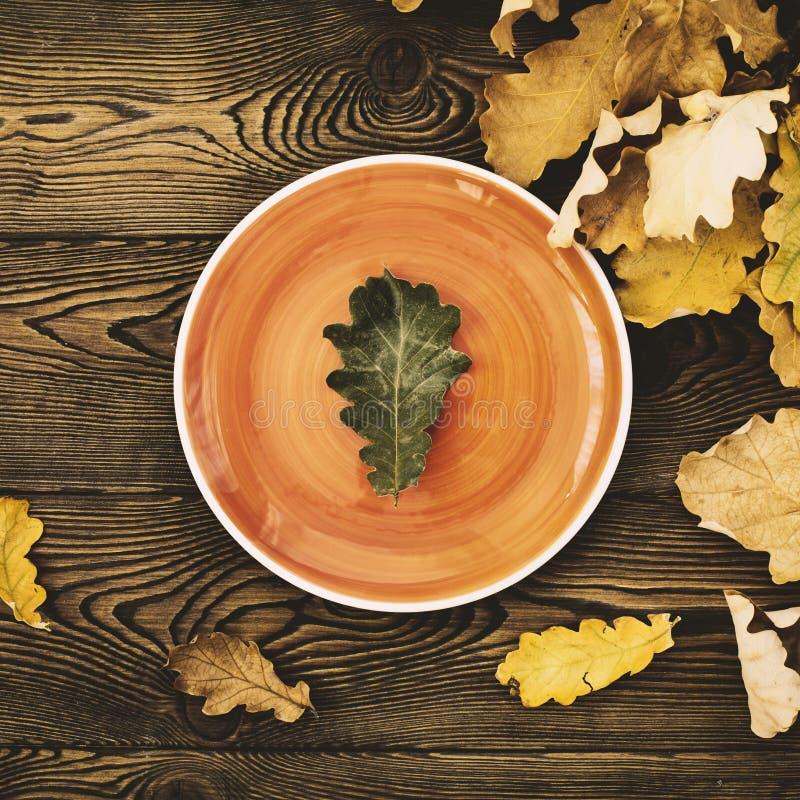 Hösttabell för tacksägelsematställe Bästa sikt av ekbladet på en orange platta och stupade kulöra sidor på en trätabell Lura royaltyfri bild