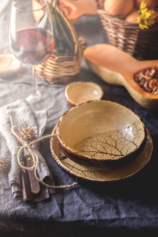 Hösttabellinställning med pumpor, korgen och rött vin Hem- garnering för nedgång för festlig matställe royaltyfri bild