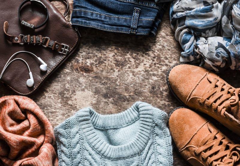 Höstuppsättning av kläder för kvinna` s - mockaskinnskor, jeans, stack sweatern, halsduken, skuldrapåsen, tillbehör på en träbakg royaltyfria bilder