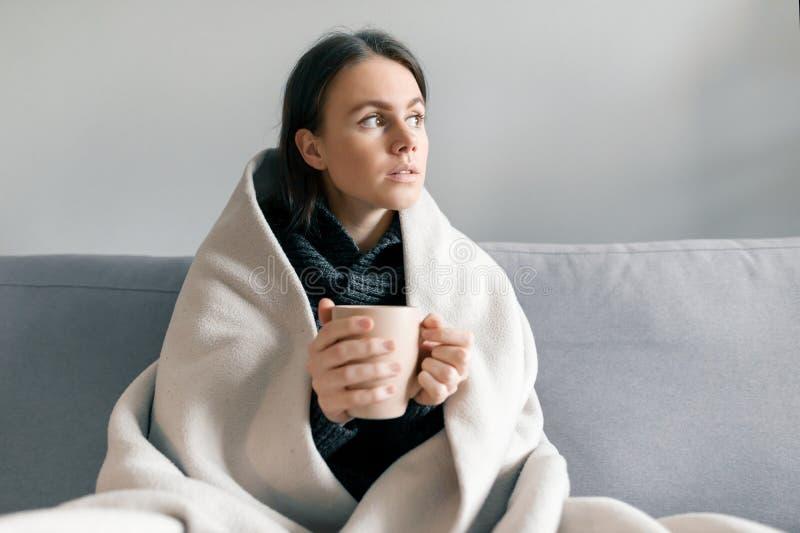 Höstvinterstående av unga flickan som hemma vilar på soffan med koppen av den varma drinken, under den varma filten royaltyfri foto