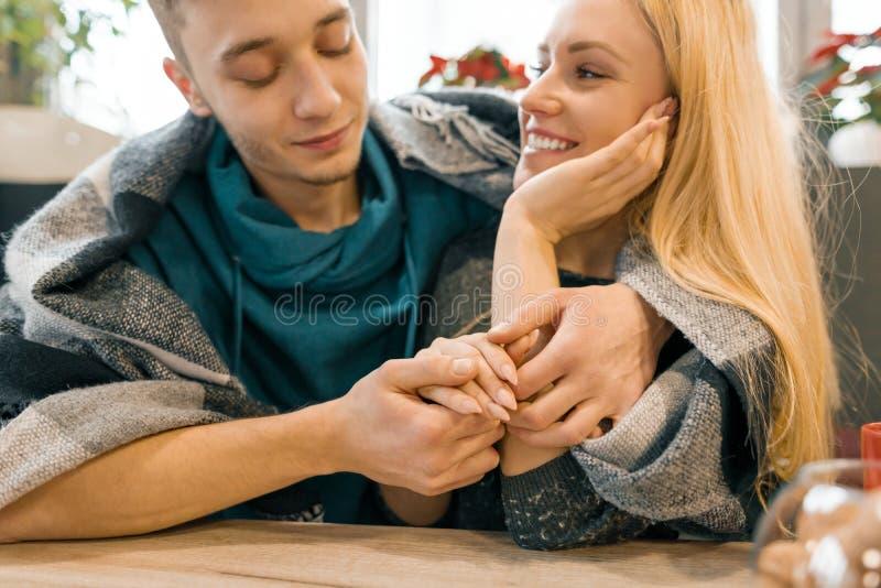 Höstvinterstående av unga omfamna par Ung man och kvinna i kafé under den varma woolen filten som dricker kaffete som är lyckligt royaltyfri fotografi