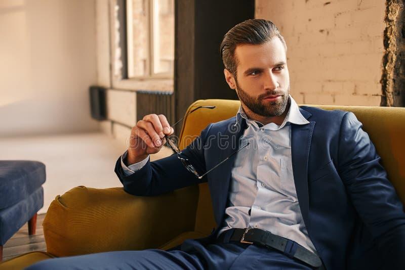 Hübsch und stilvoll Junge Klage des Geschäftsmannes in Mode hält Gläser, sitzt auf Sofa und denkt ungefähr stockfotos
