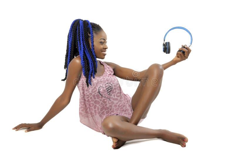 Hübsche Afroamerikanerfrau, die einen Kopfhörer hält lizenzfreies stockbild