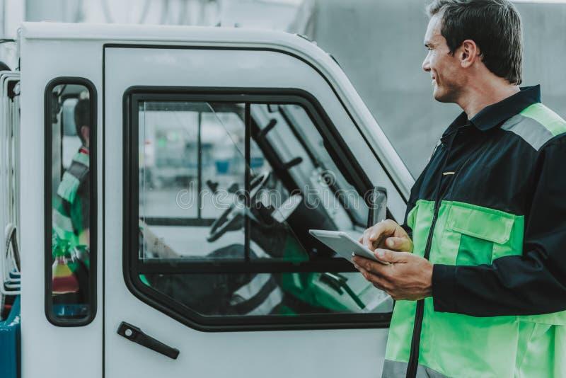 Hübsche Arbeitskraft, die den Transport auf dem Arbeitsplatz betrachtet stockfotografie