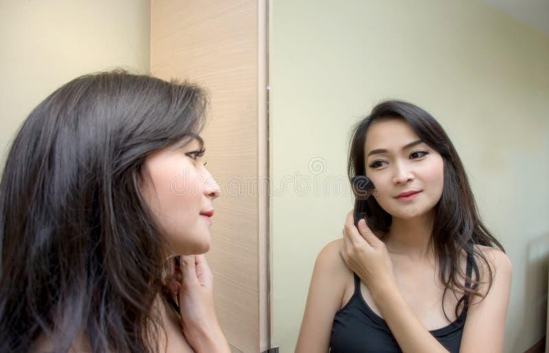 Hübsche Asiatin am Spiegel, der kosmetischen Pinsel an ihrem Gesicht anwendet lizenzfreie stockfotografie