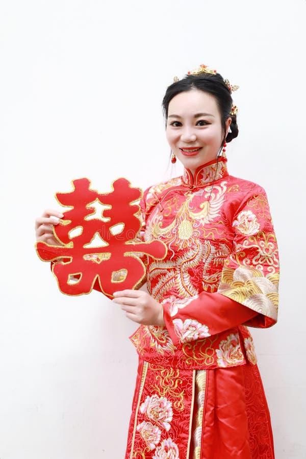 Hübsche asiatische chinesische schöne Braut mit traditionellem chinesischem rotem Kleid der Hochzeit und doppeltem Glück zwei stockbild