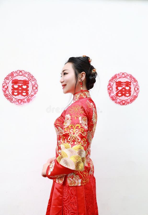 Hübsche asiatische chinesische schöne Braut mit traditionellem chinesischem rotem Kleid der Hochzeit und doppeltem Glück zwei stockfotografie