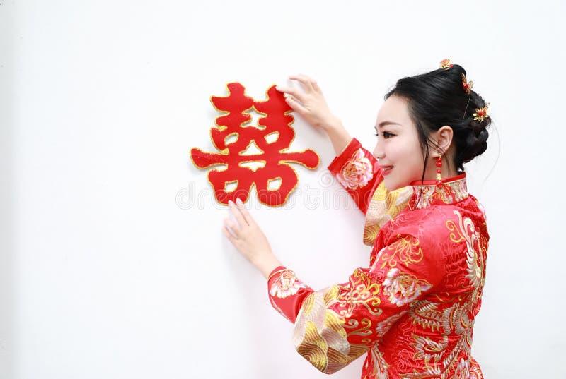 Hübsche asiatische chinesische schöne Braut mit traditionellem chinesischem rotem Kleid der Hochzeit und doppeltem Glück zwei lizenzfreies stockbild