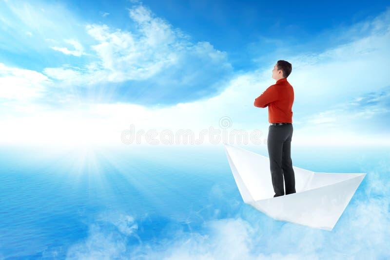 Hübsche asiatische Geschäftsmannstellung auf Papierbootssegeln auf blauem Ozean stockfoto