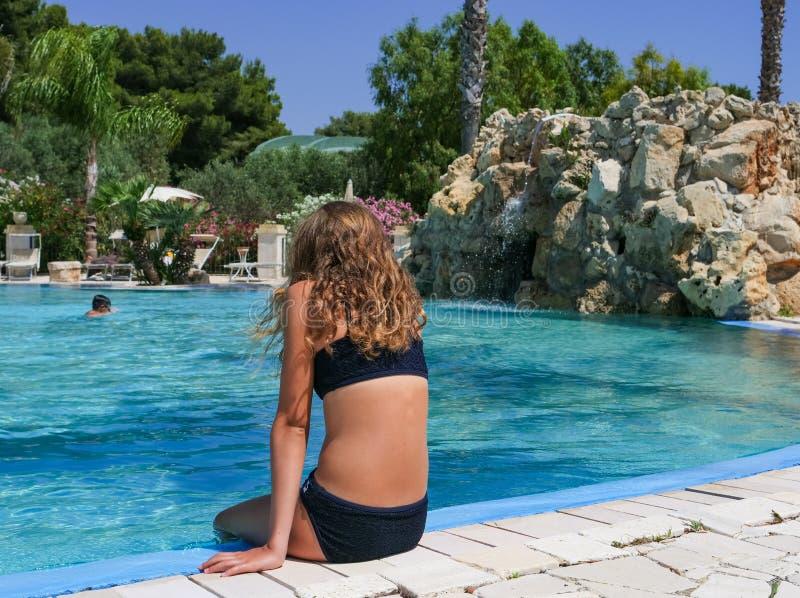 Hübsche athletische Sonne bräunte das Mädchen, das im Urlaub in einem Swimmingpool sitzt stockbild