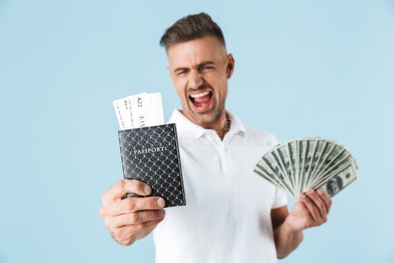Hübsche aufgeregte emotionale erwachsene Mannaufstellung lokalisiert über blauem Wandhintergrund-Holdingpaß mit Karten und Geld lizenzfreie stockfotografie