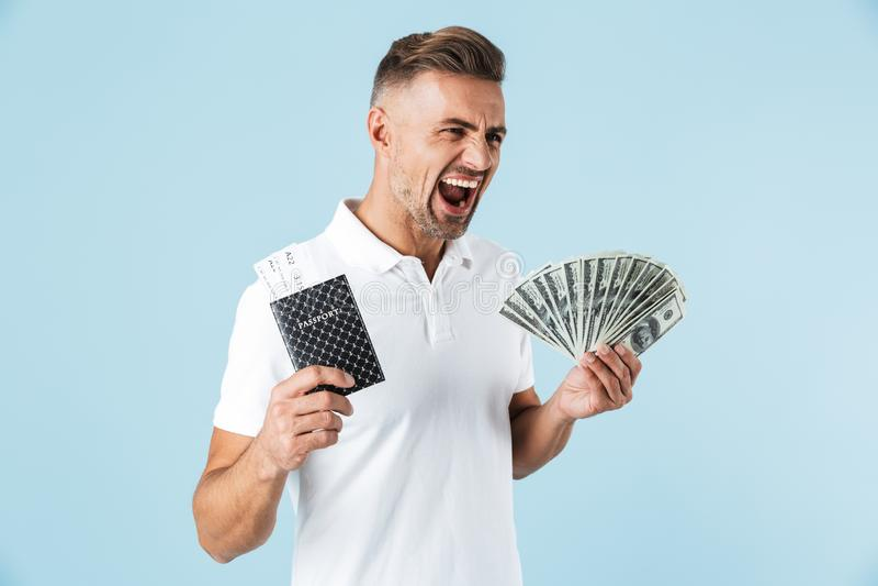 Hübsche aufgeregte emotionale erwachsene Mannaufstellung lokalisiert über blauem Wandhintergrund-Holdingpaß mit Karten und Geld lizenzfreie stockbilder