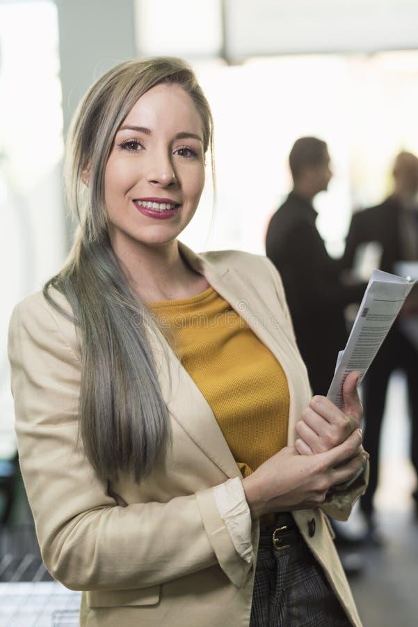 Hübsche BüroArbeitnehmerin, die Kamera im Büro betrachtet stockfotografie