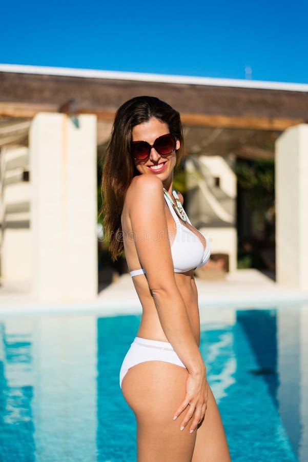 Hübsche Bikinifrau, die am Poolside auf Sommerferien sich entspannt stockfoto