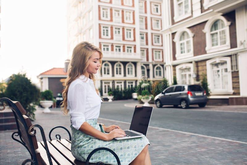 Hübsche blonde Geschäftsfrau, die an Laptop auf banch in der Stadt arbeitet Sie trägt weißes Hemd, blauen Rock, schaut beschäftig lizenzfreie stockfotografie
