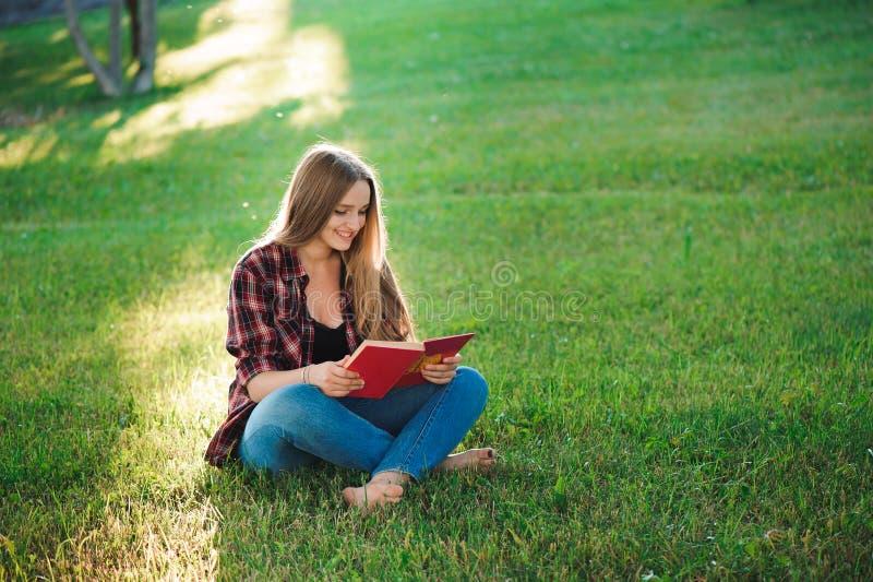 Hübsche blonde junge Frau, die ein Buch am Park liest lizenzfreie stockfotografie