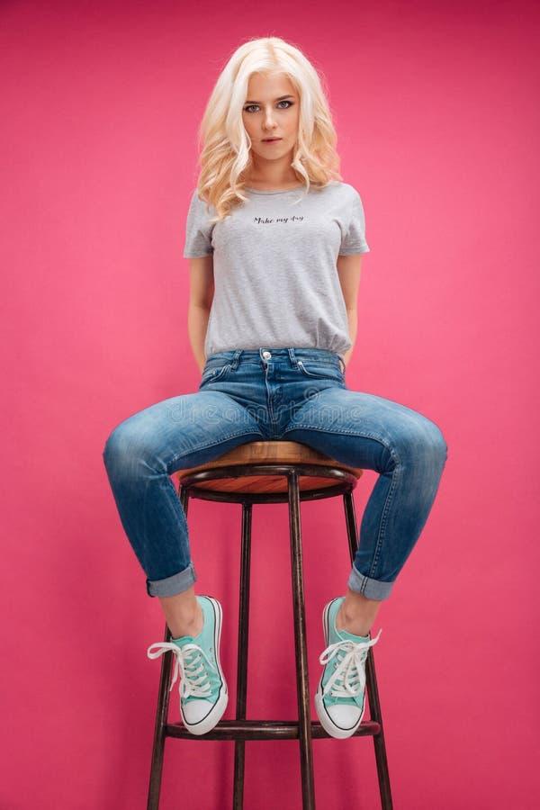 Hübsche Blondine, die auf dem Stuhl sitzen lizenzfreies stockfoto