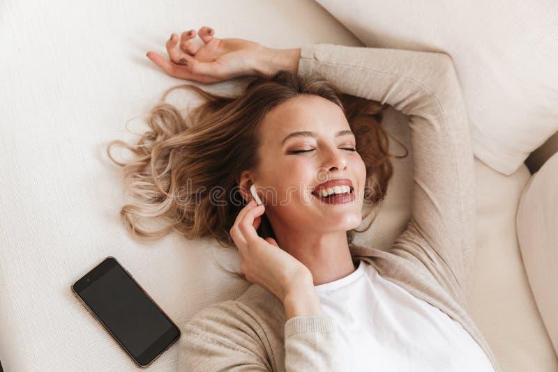 Hübsche Blondine, die hörende Musik mit Kopfhörern zuhause zu Hause sitzend aufwerfen lizenzfreie stockbilder