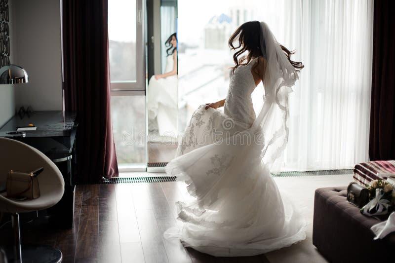 Hübsche Braut im weißen Kleid und im Schleiertanzen nahe dem Fenster stockbild