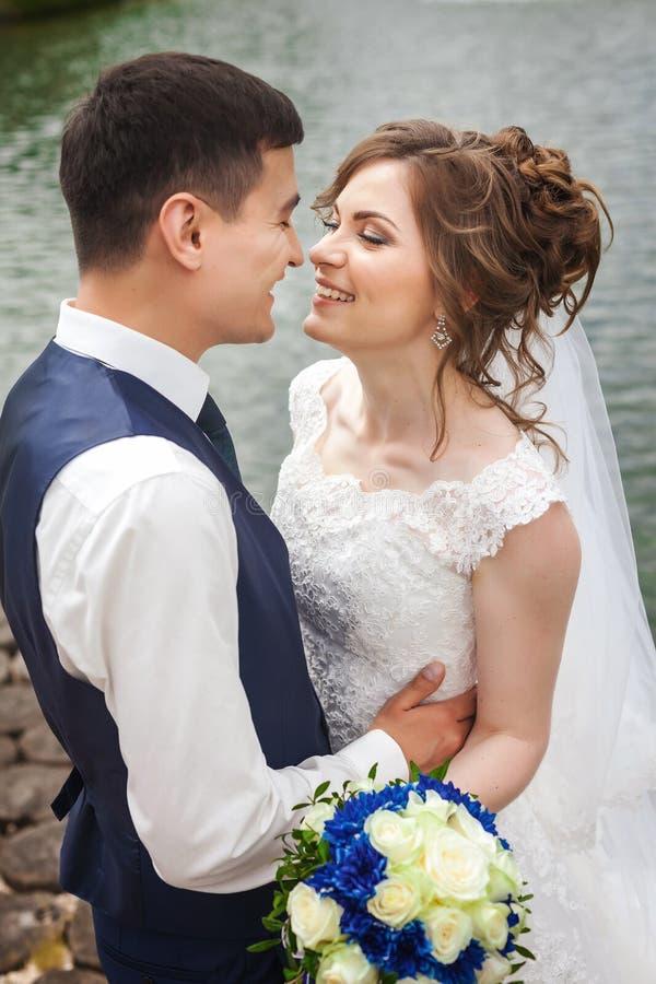 Hübsche Braut und Bräutigam, die nahe dem See lächelt lizenzfreies stockbild