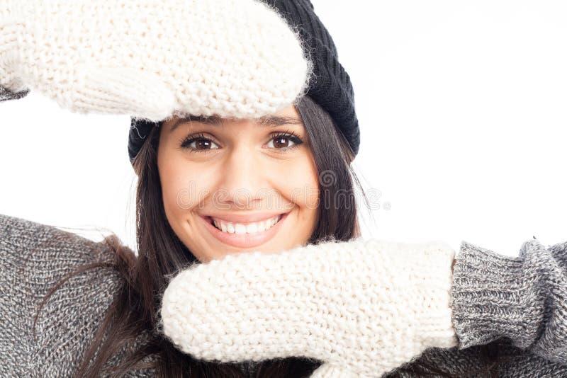 Hübsche brunette Frau mit einem woolen Hut ein Strickjacken- und Handschuhlächeln lizenzfreie stockfotos