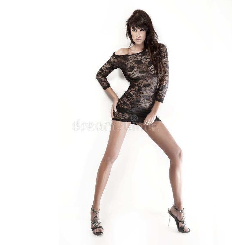 Hübsche Brunettedame, die kurzes schwarzes Kleid trägt und über w aufwirft stockfotografie