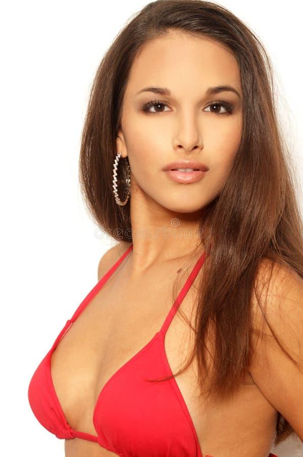 Hübsche Brunettefrau in der roten Bikinioberseite stockfoto