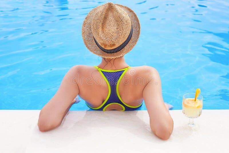 Hübsche Brunettefrau, die Limonade in einem Swimmingpool genießt stockbild