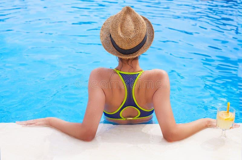 Hübsche Brunettefrau, die Limonade in einem Swimmingpool genießt lizenzfreie stockfotografie