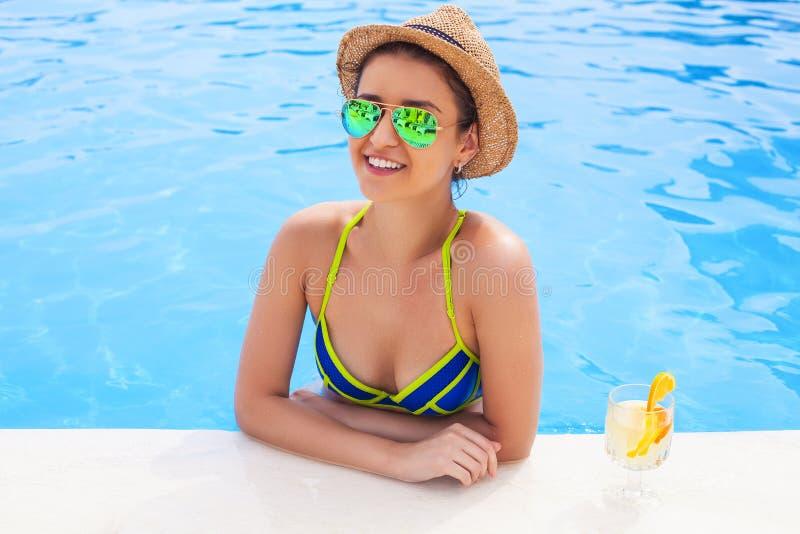 Hübsche Brunettefrau, die Limonade in einem Swimmingpool genießt lizenzfreies stockfoto