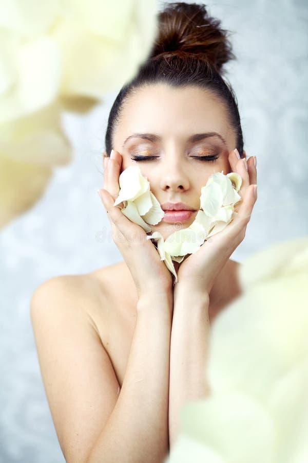 Hübsche Brunetteholdingblumenblätter Nah An Gesicht Stockfoto