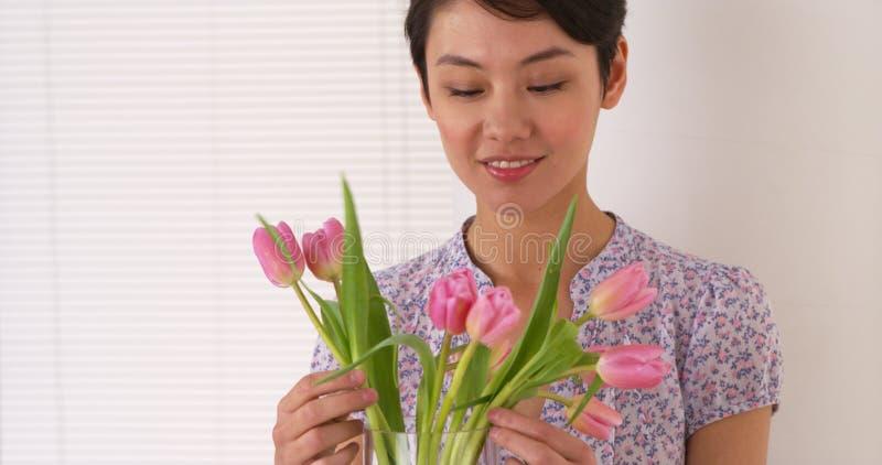 Hübsche Chinesin, die Tulpen vereinbart lizenzfreies stockfoto