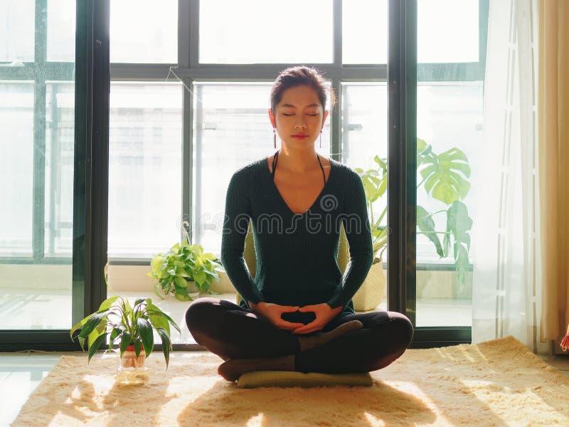 Hübsche chinesische junge Frau, die zu Hause, sitzend auf Boden mit Pelzkissen im Sonnenlicht, Übung, Lotus-Haltung, Gebet mediti stockfoto