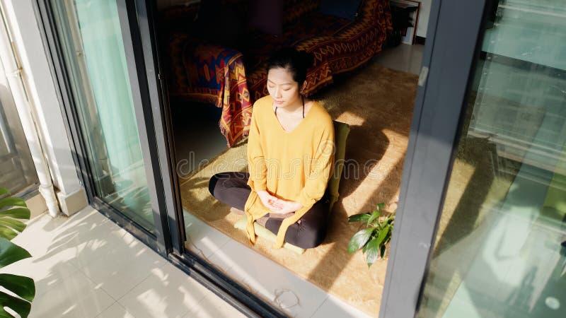 Hübsche chinesische junge Frau, die zu Hause, sitzend auf Boden mit Pelzkissen im Sonnenlicht meditiert stockbild