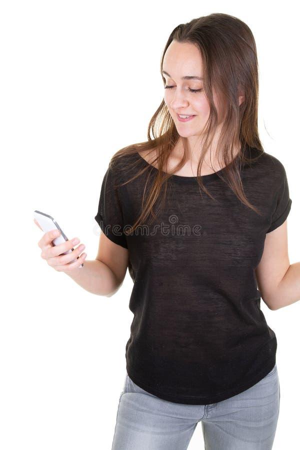 Hübsche dünne junge Frau, die mit Mobil-Telefon gegen weißen Hintergrund lächelt lizenzfreie stockfotografie